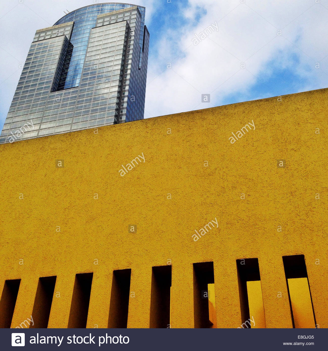 Upward view of yellow wall by tower - Stock Image