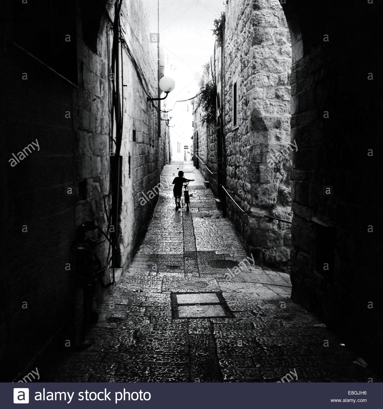 Rear view of boy with bike on street - Stock Image