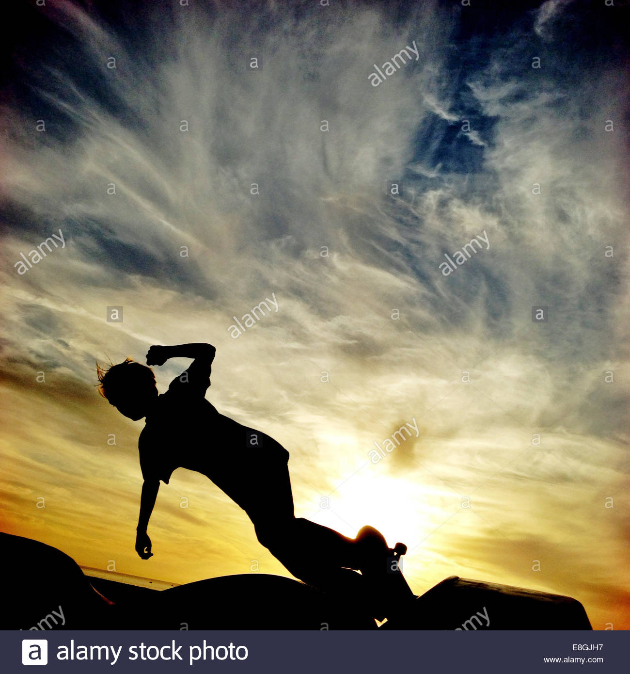 Silhouette of a boy skateboarding - Stock Image