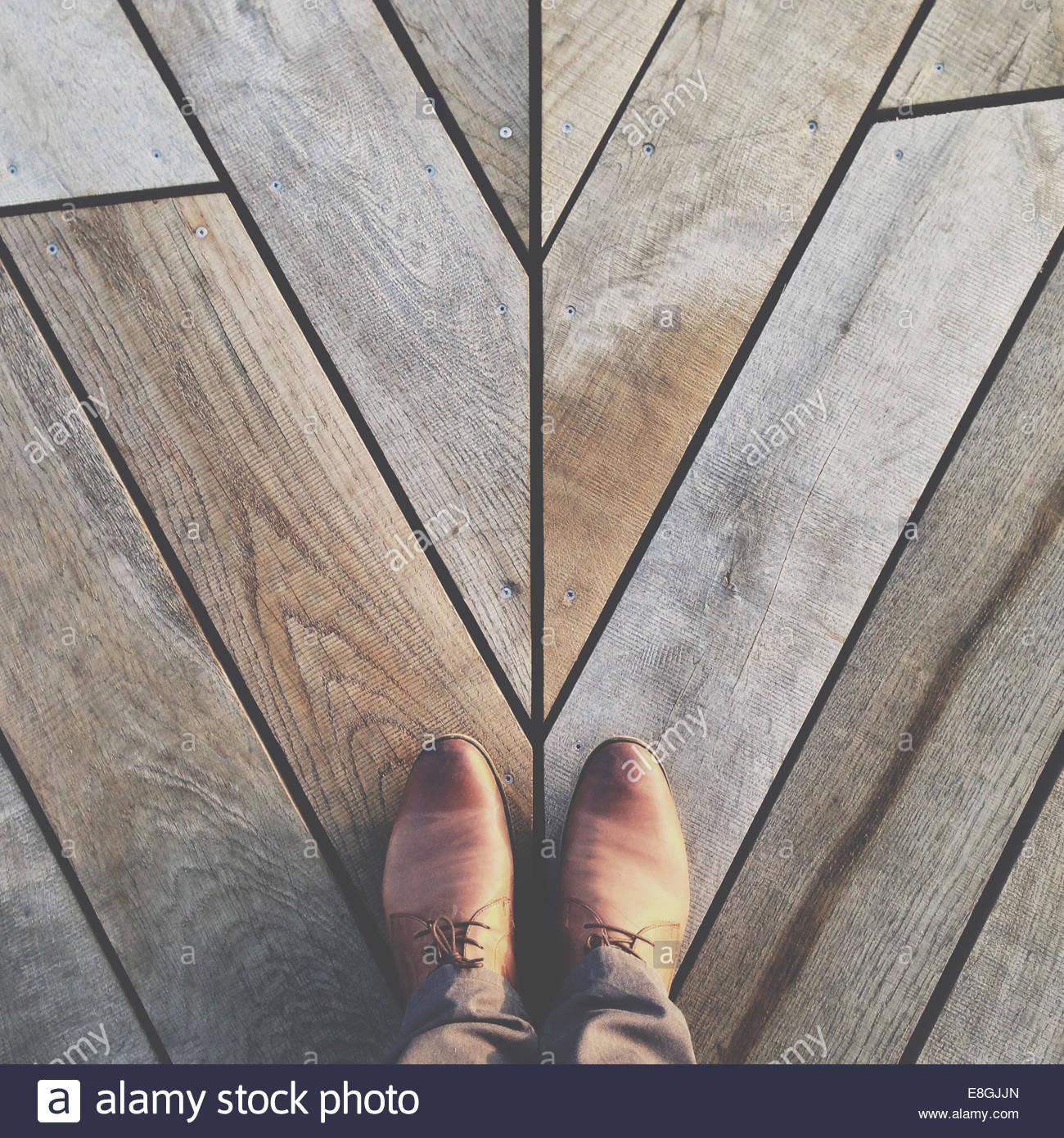 Feet on hardwood floor - Stock Image