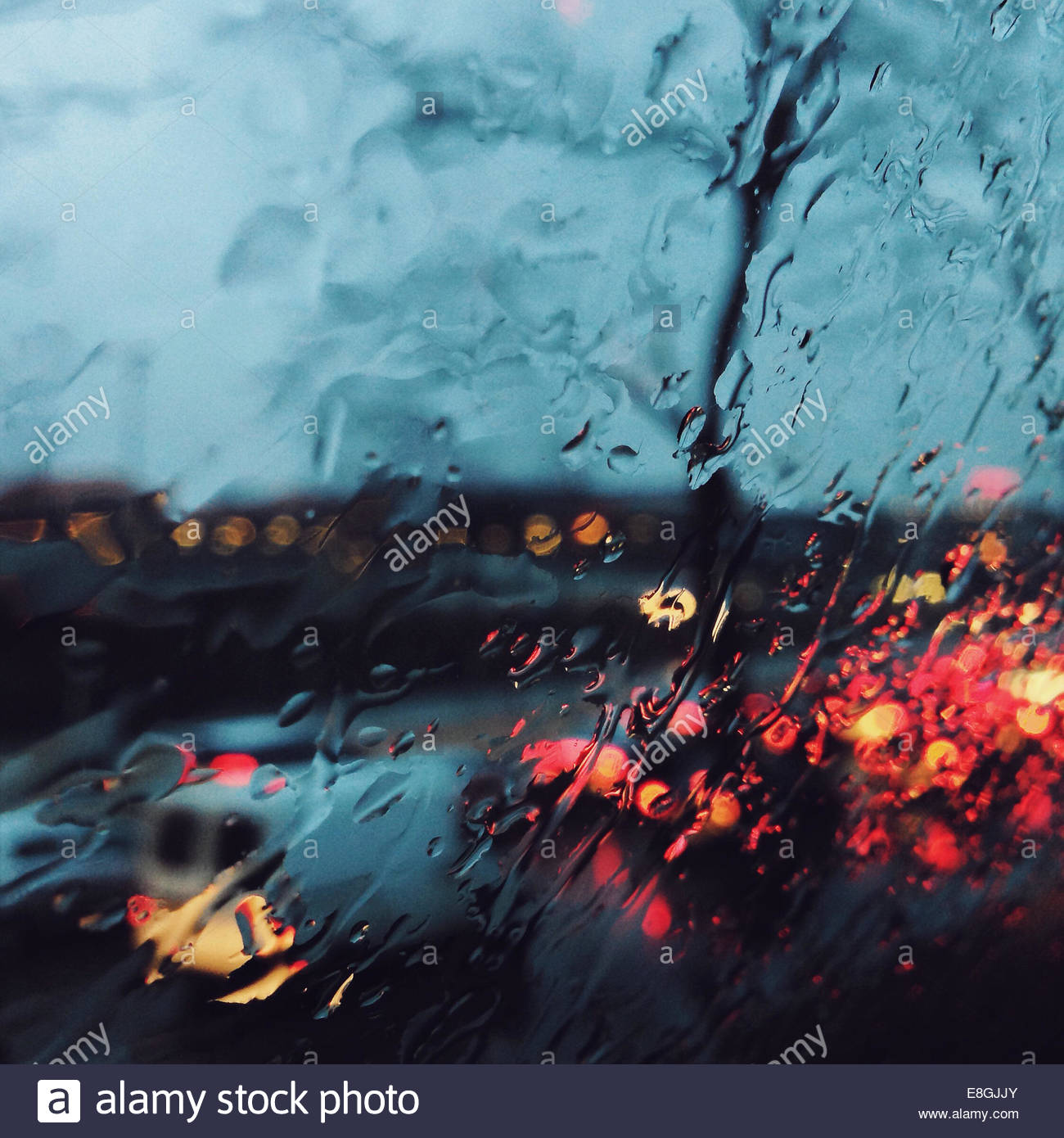 Rain streaked window with street view - Stock Image