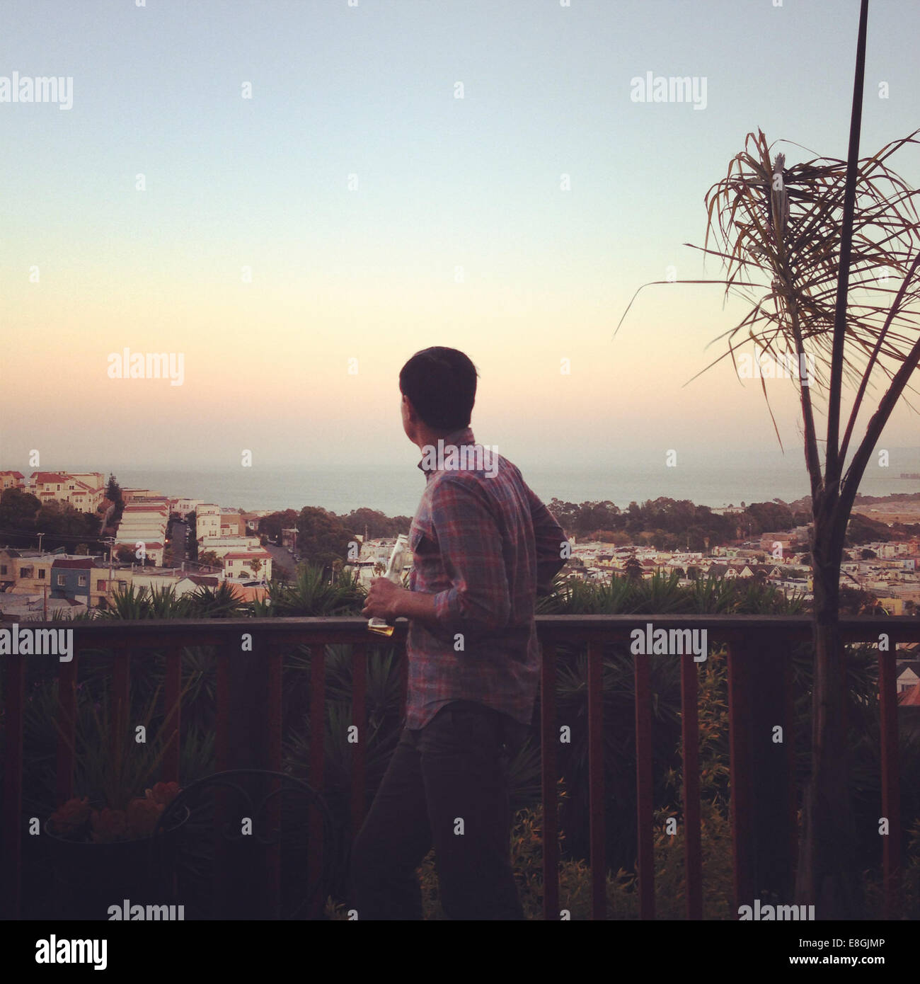 Man standing on a balcony looking at sunset, San Francisco, California, America, USA - Stock Image