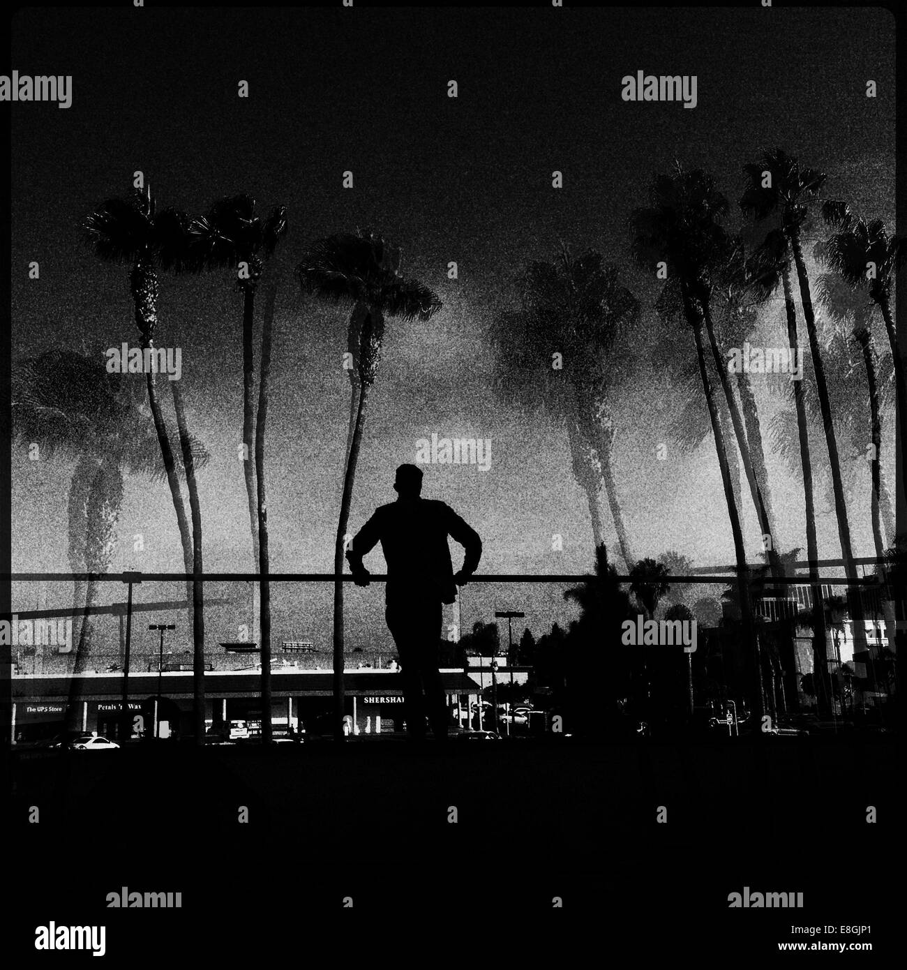 Silhouette of a man looking over balcony - Stock Image