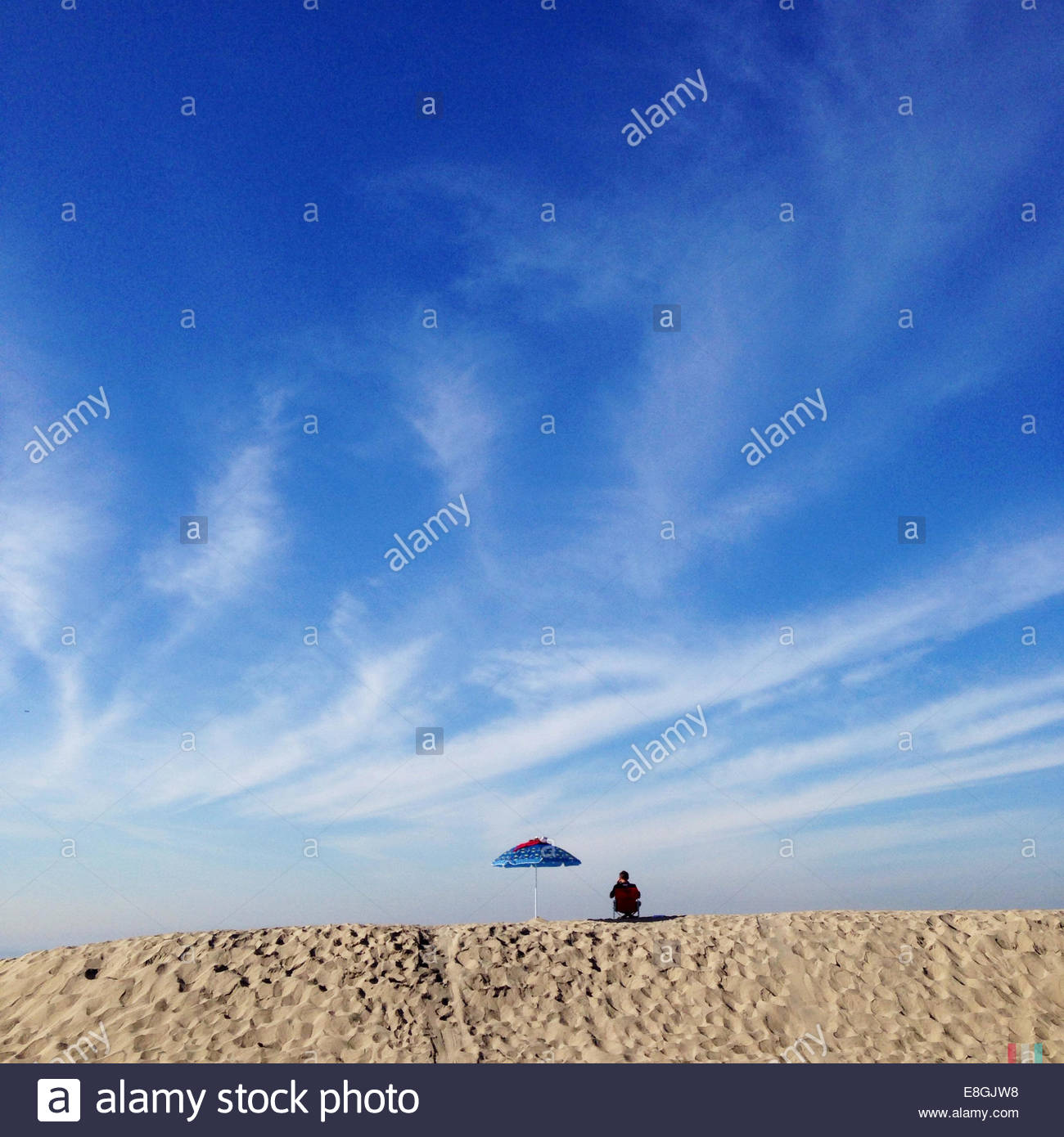 Rear view of man sitting on beach - Stock Image