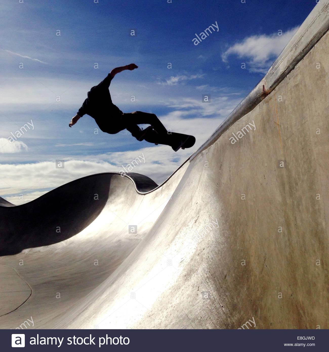 Skater jumping in skateboard park - Stock Image