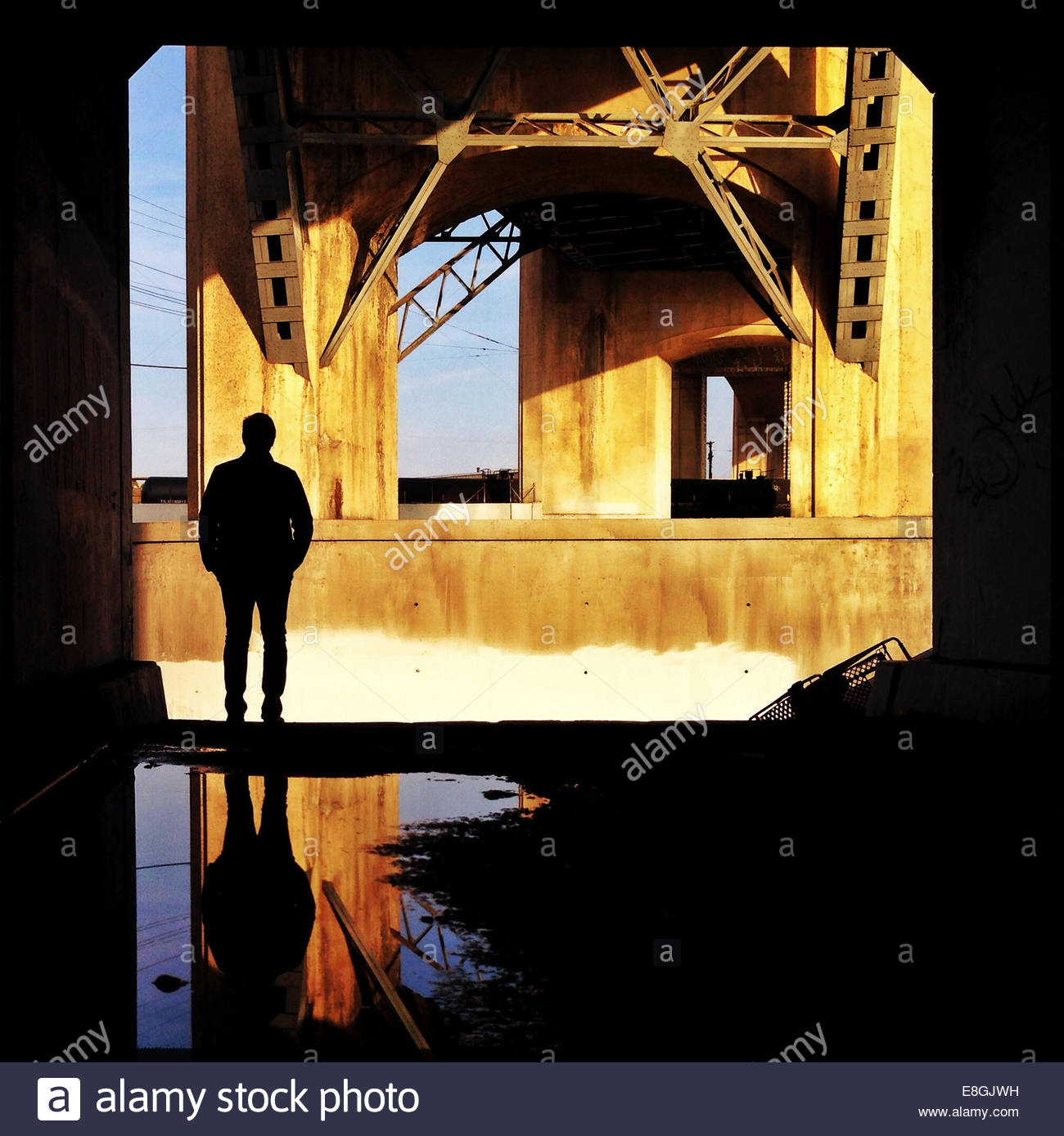 Silhouette of man standing under bridge - Stock Image
