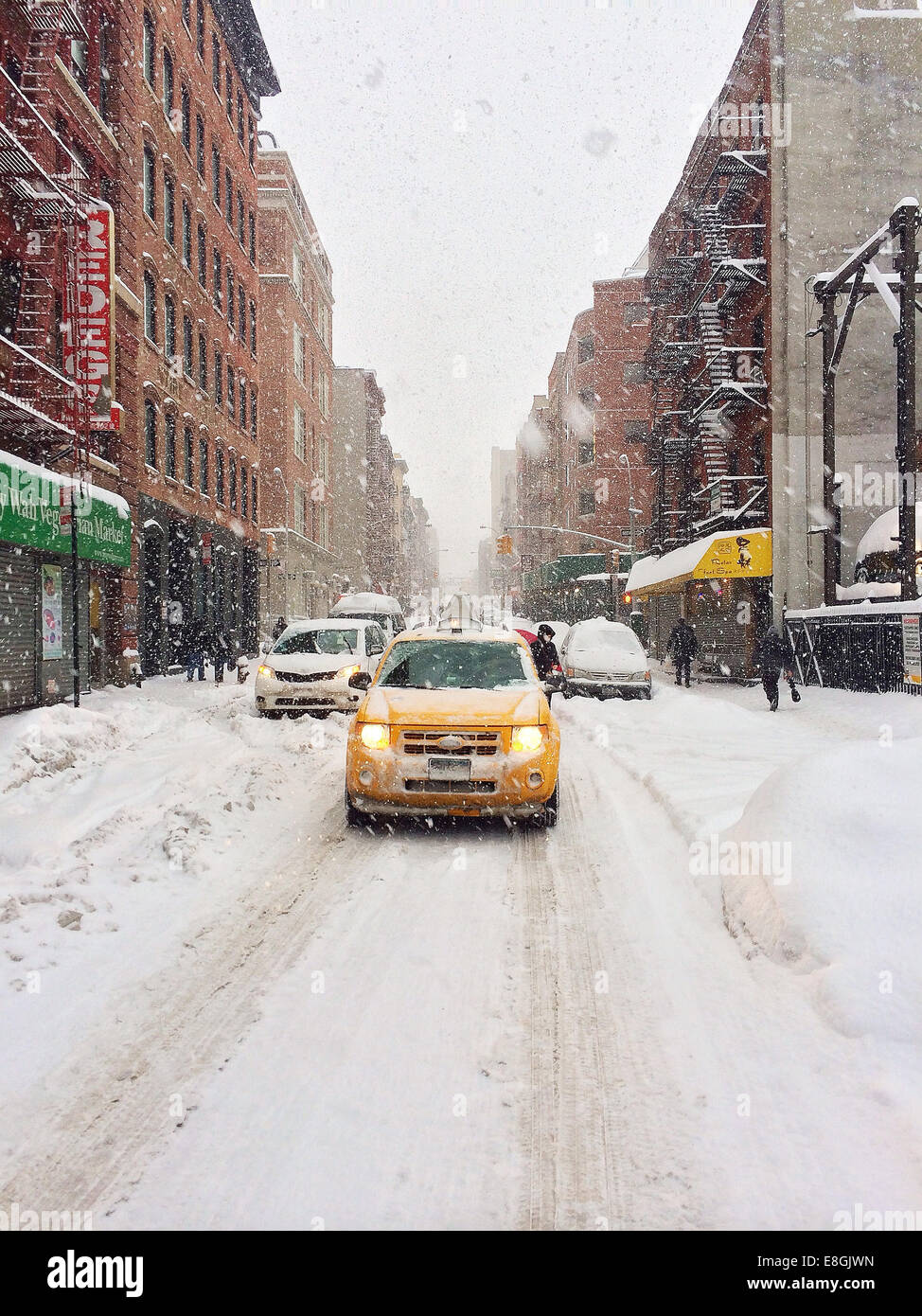 USA, New York City, Lower East Side, Chinatown, Yellow cab in snowstorm - Stock Image