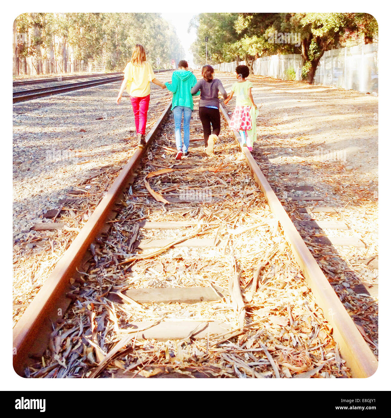 Four children walking along railway tracks - Stock Image