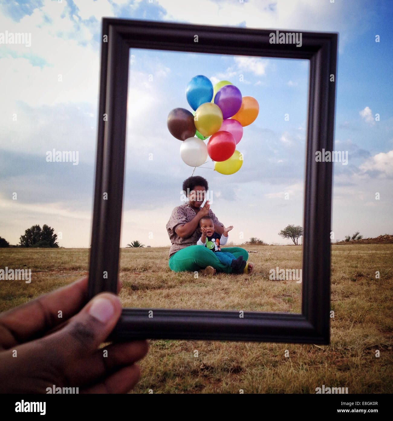 Man holding a Picture frame in front of a Mother and son in a meadow, Roodeport, Johannesburg, Gauteng, South Africa Stock Photo
