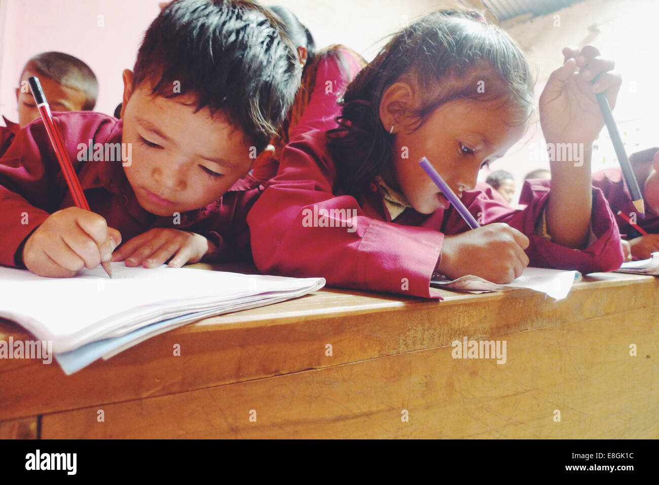 School children writing in classroom, Nepal Stock Photo