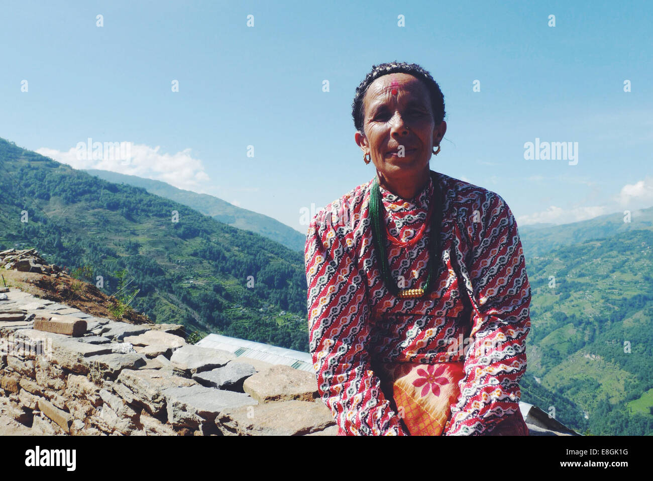 Portrait of woman sitting on stone wall in mountains - Stock Image