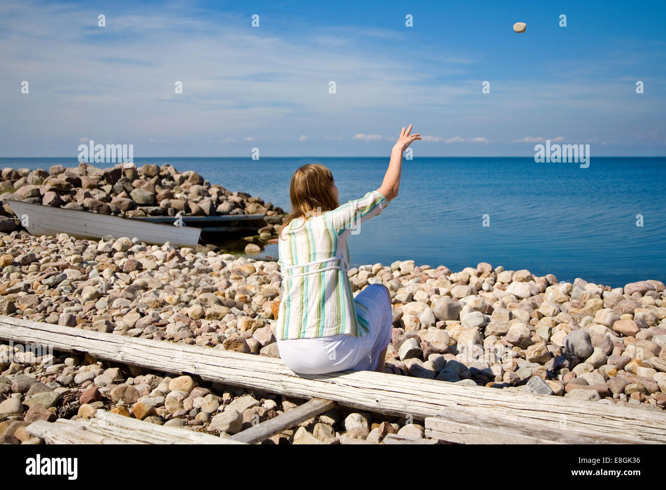 Woman throwing rock on rocky beach - Stock Image