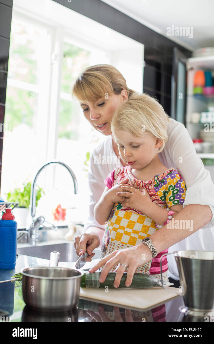 Mother teaching daughter to cut vegetables in kitchen - Stock Image