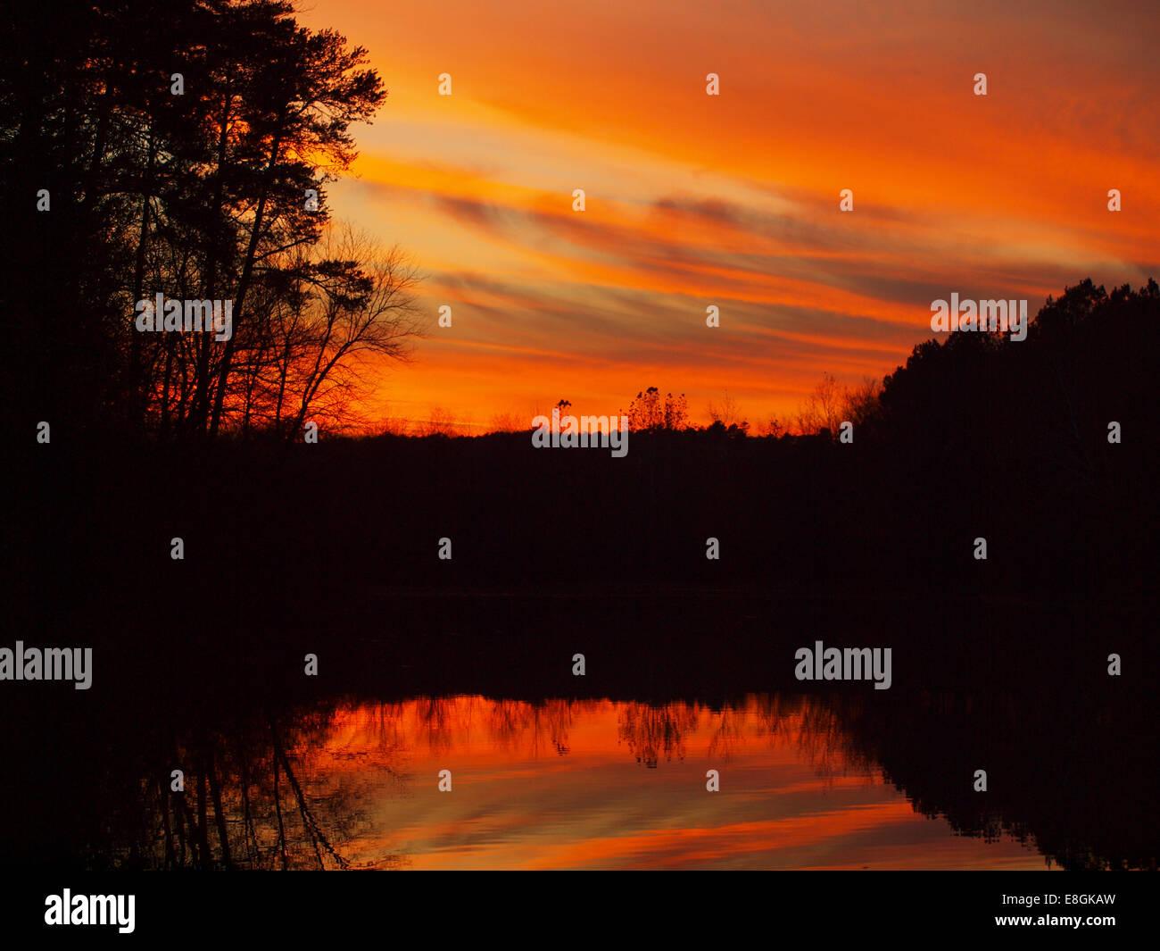 USA, North Carolina, Iredell County, Statesville, Sunset reflection on lake - Stock Image
