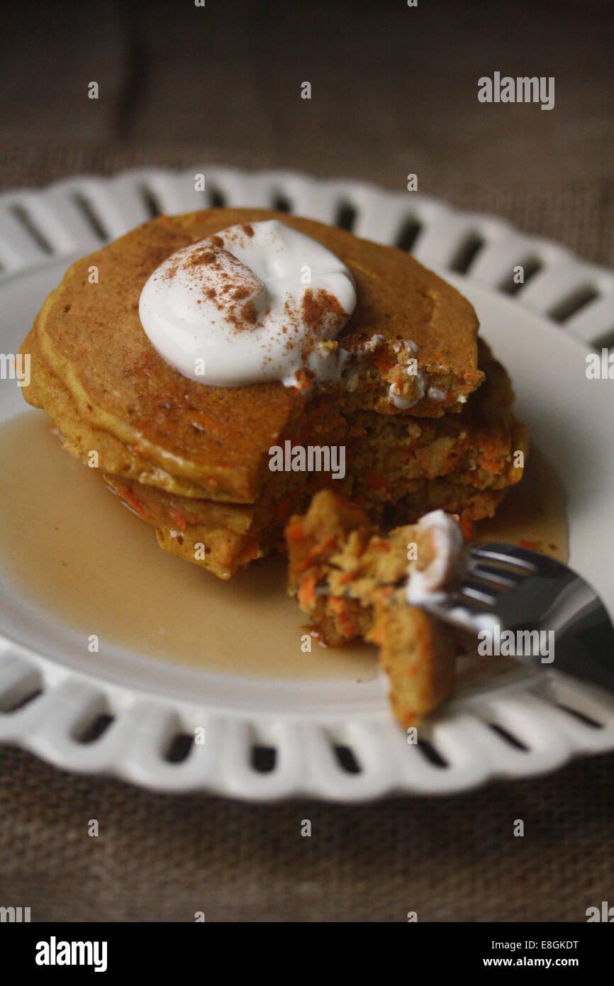 Carrot cake pancakes with yogurt, warm maple syrup and cinnamon - Stock Image