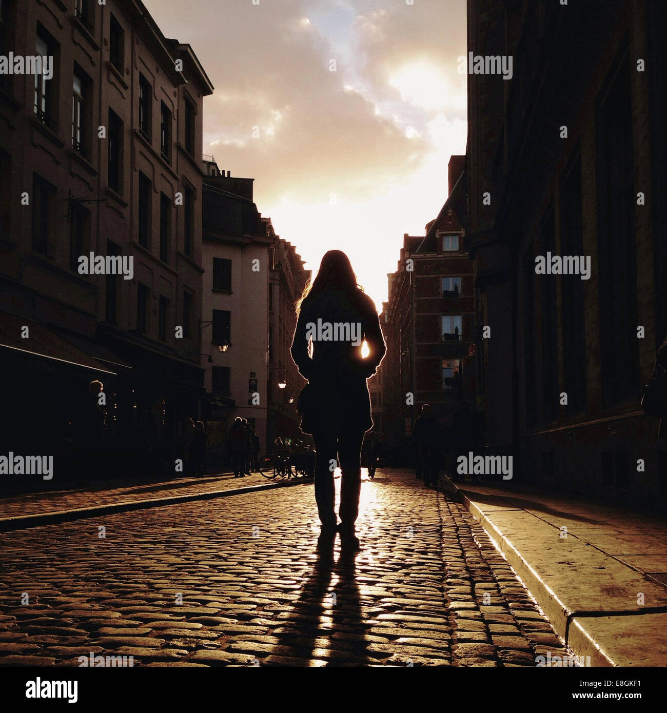 Rear view of woman standing in street Stock Photo