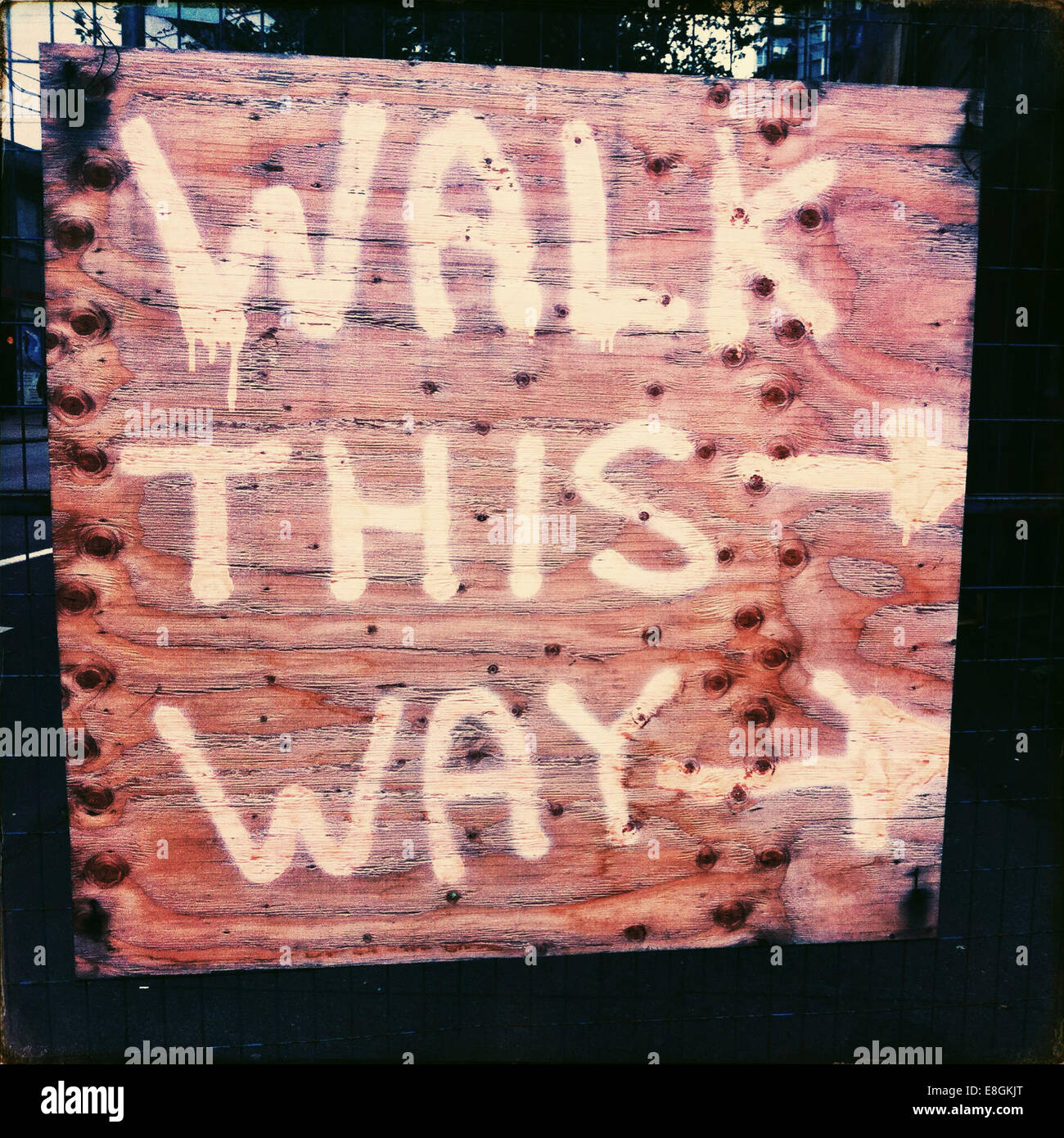 Walk this way Direction sign on sidewalk near construction site - Stock Image