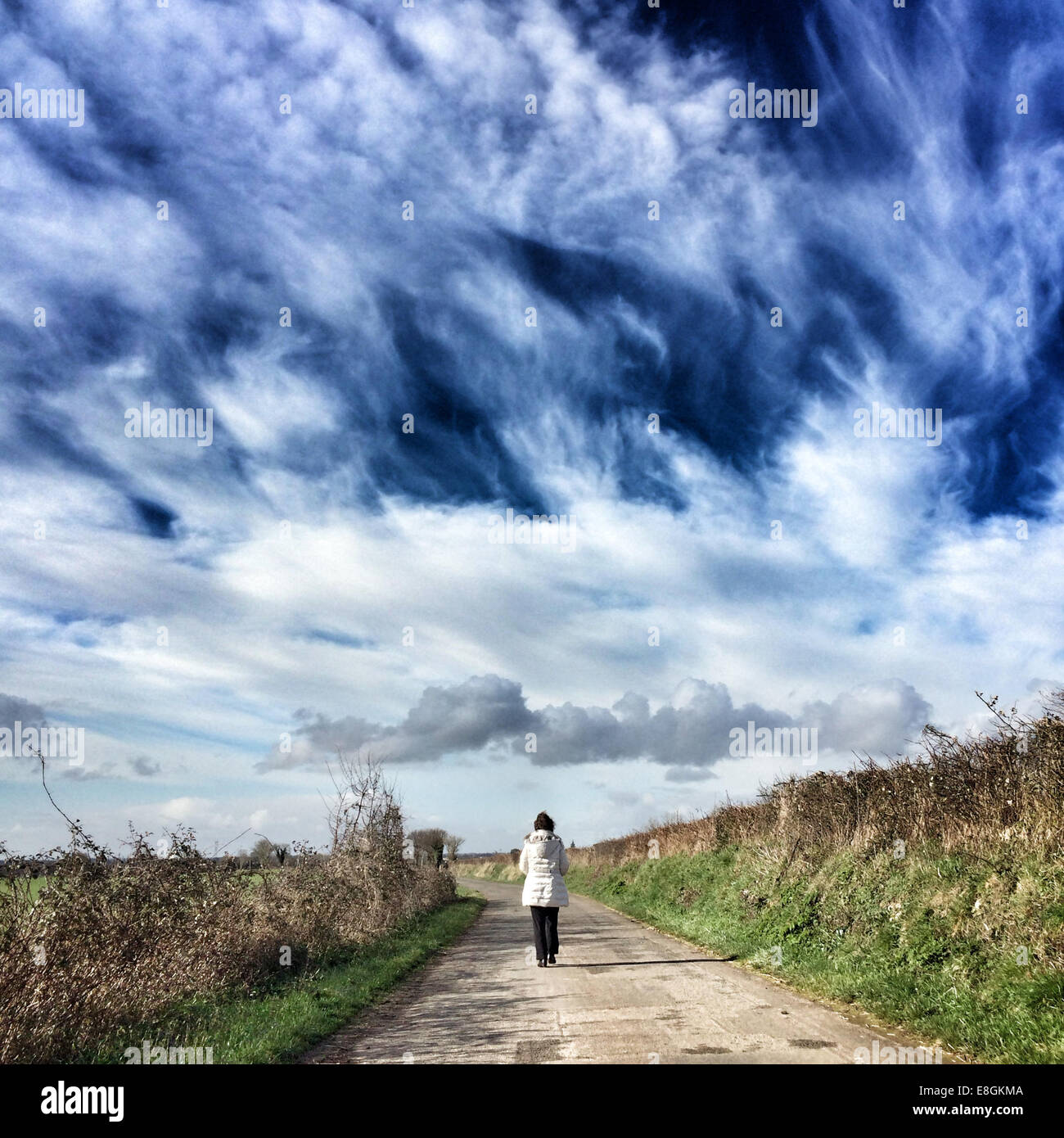 Woman walking down path - Stock Image