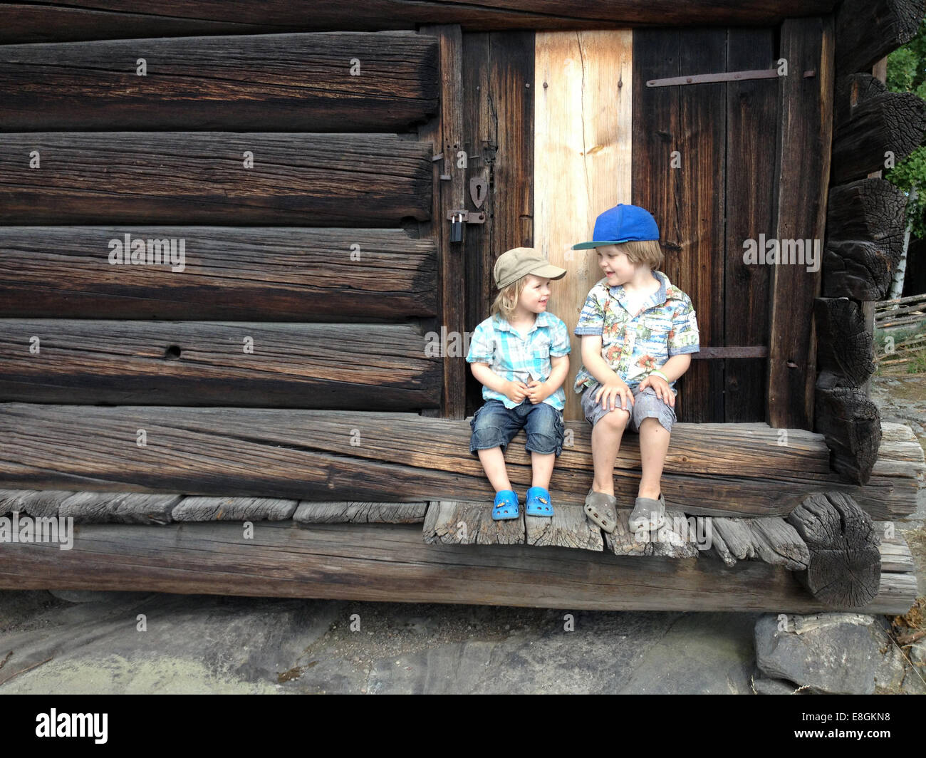 Two boys sitting on porch steps talking - Stock Image