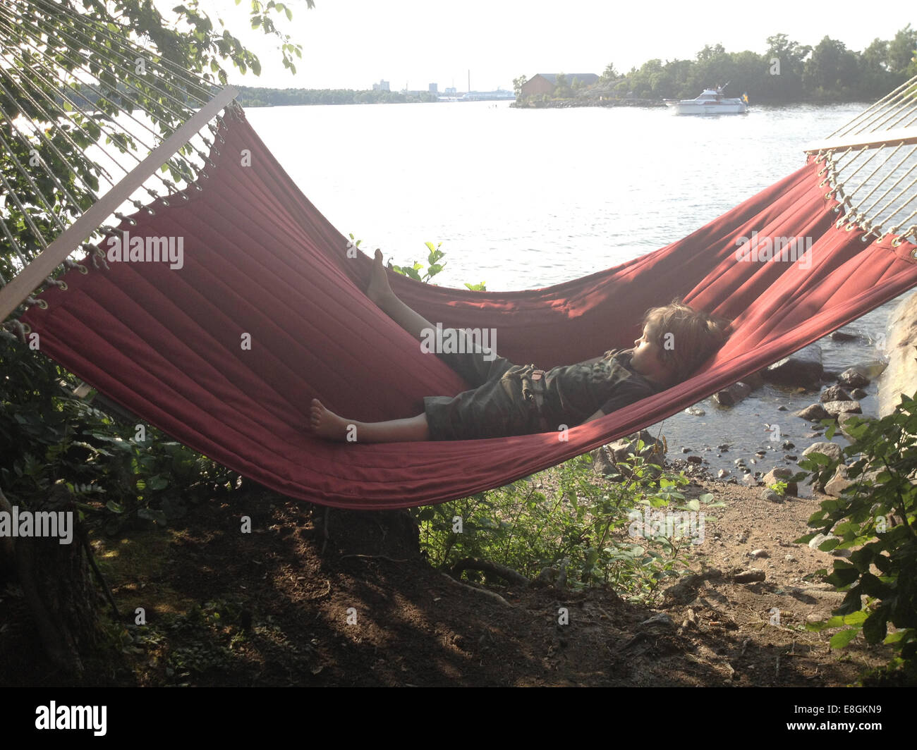 Little Boy Resting In Hammock On A Beautiful Summer Day By The Water - Stock Image