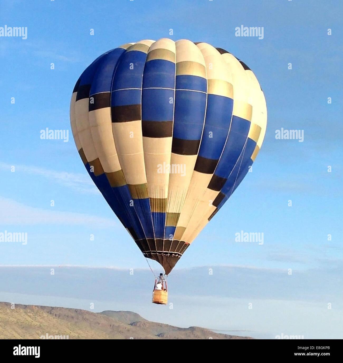 Hot air balloon flying mid air - Stock Image