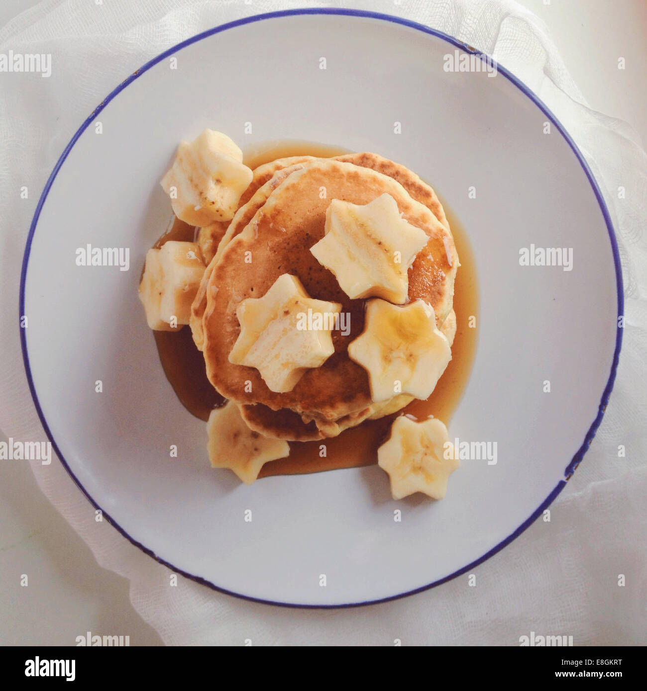 Stack of pancakes with banana and maple syrup - Stock Image
