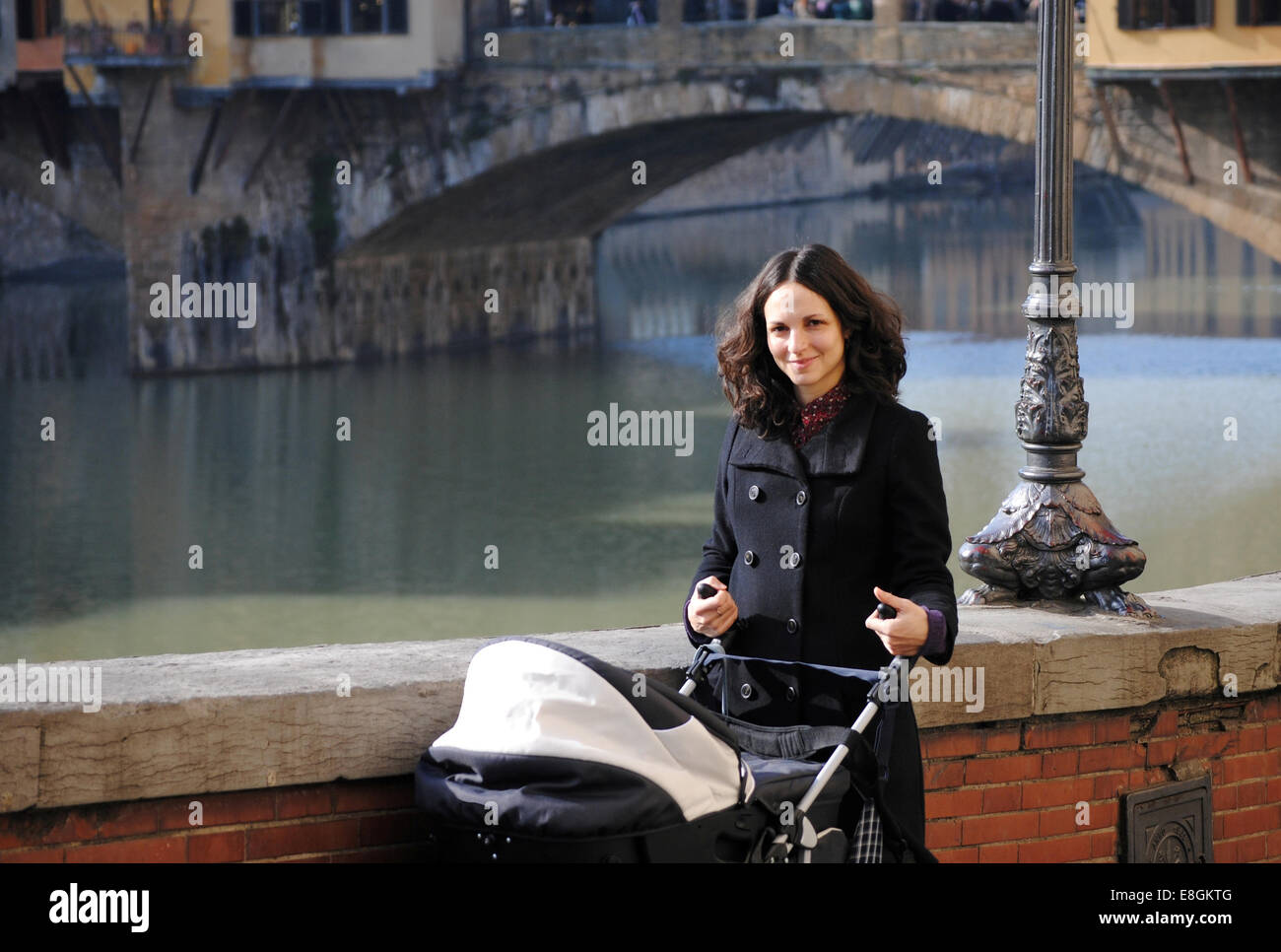 Mother pushing a pram near Ponte Vecchio, Florence, Tuscany, Italy - Stock Image