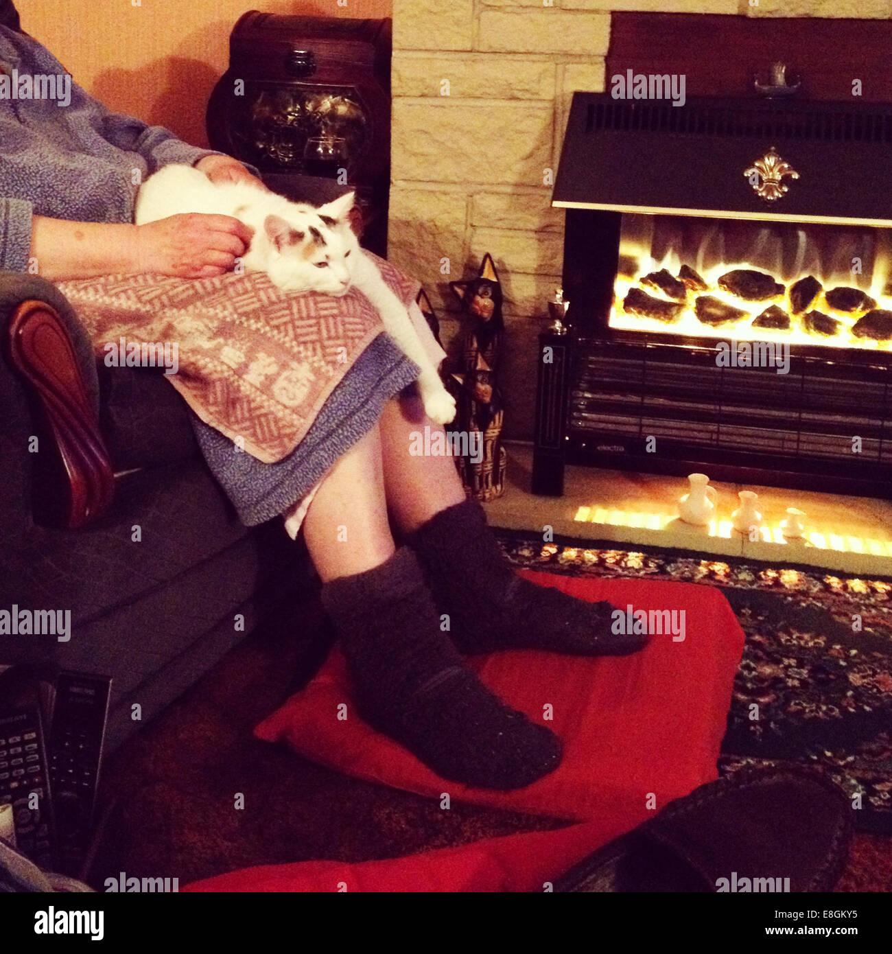 Cat lying on woman's lap - Stock Image