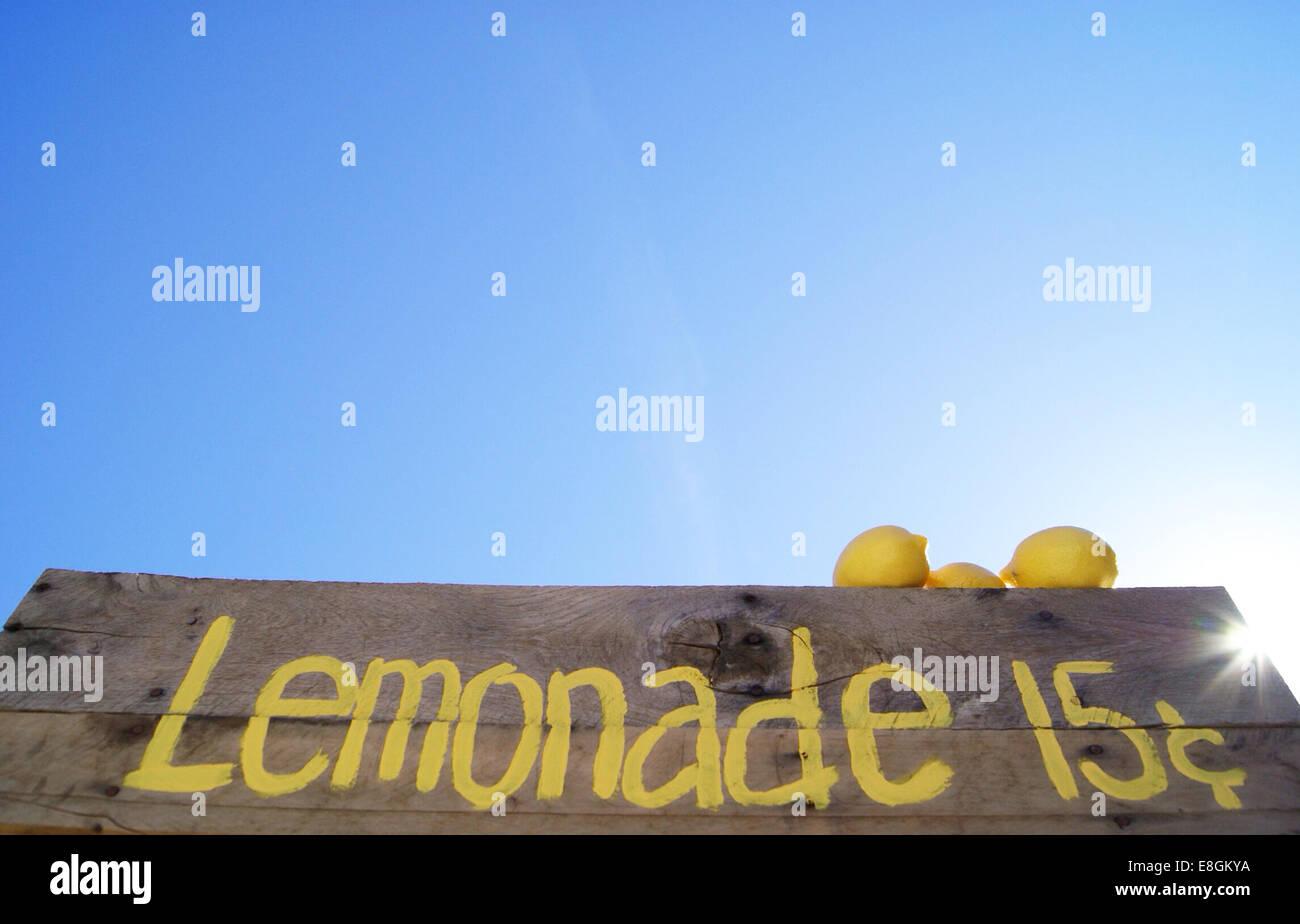 Lemonade stand sign with fresh lemons - Stock Image