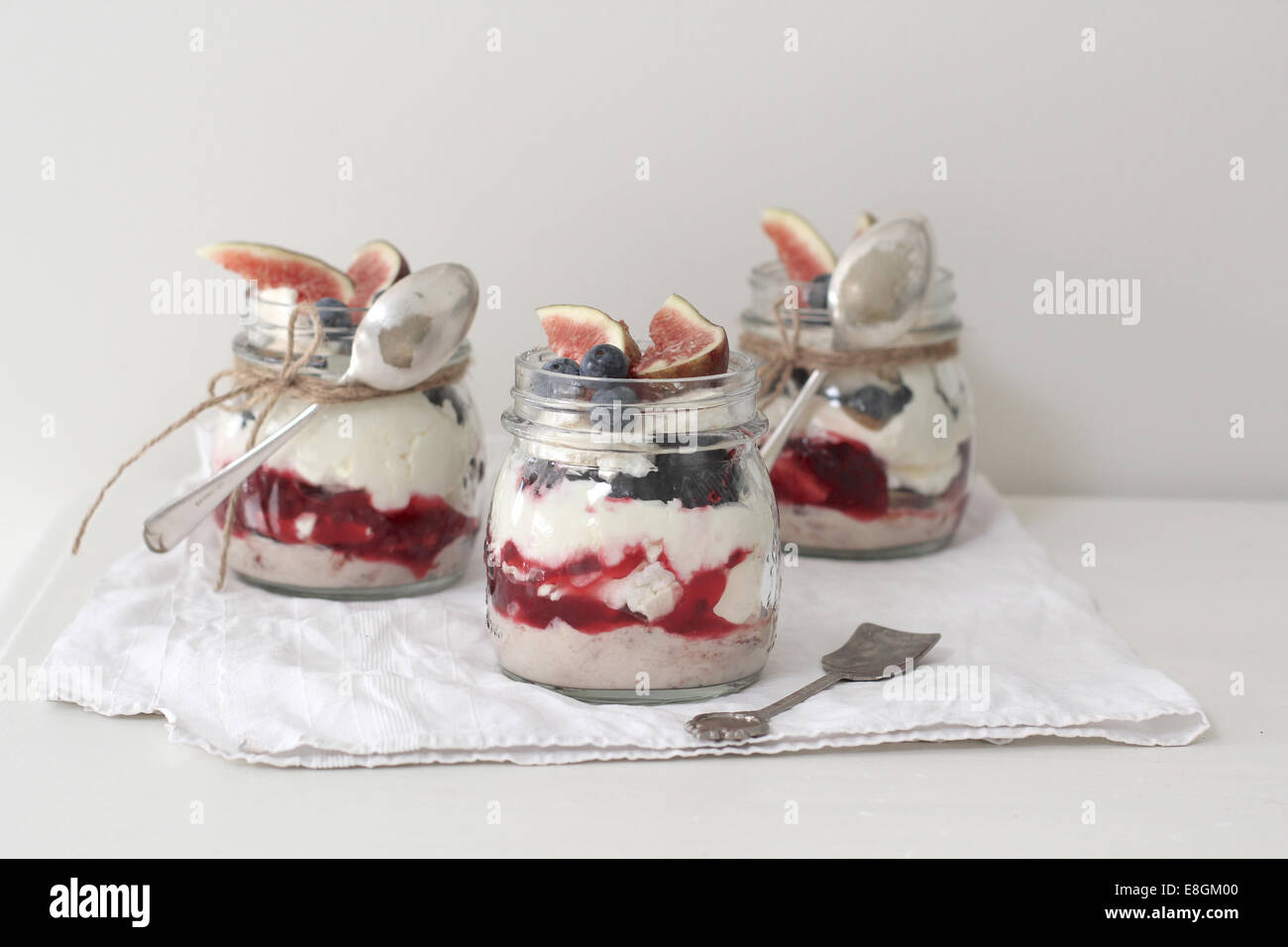 Eton mess desserts in jars topped with fresh figs and blueberries - Stock Image