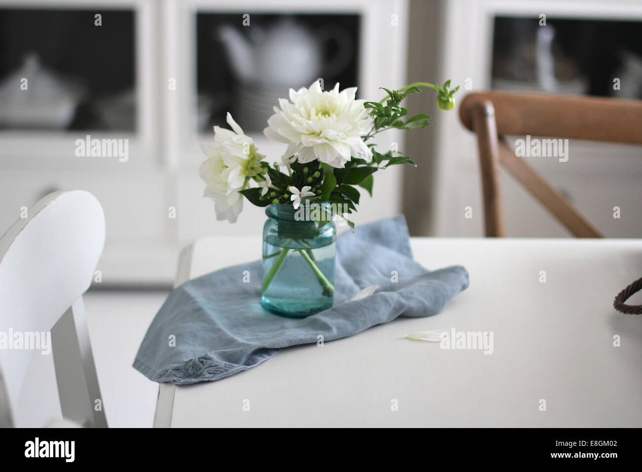 Vase of flowers and napkin on dining room table - Stock Image