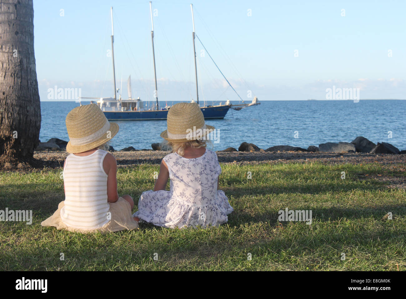 Two girls sitting on grass looking at boat, Port Douglas, Queensland, Australia - Stock Image