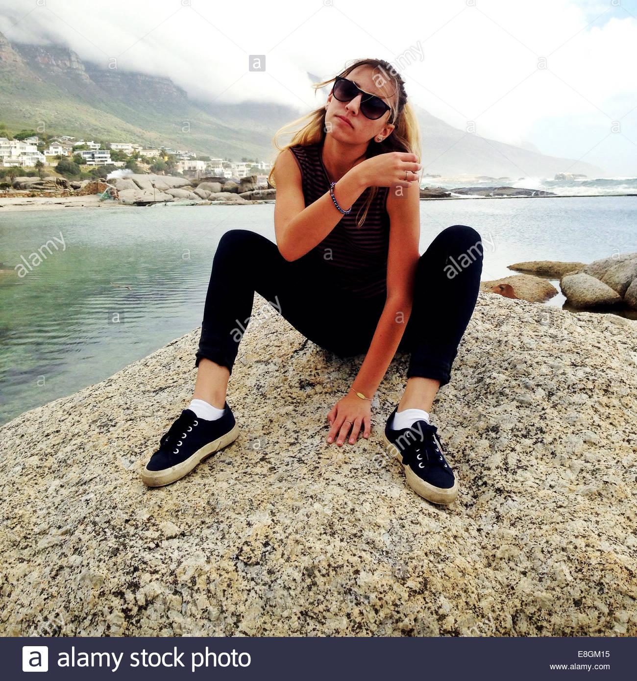 Woman sitting on rock - Stock Image