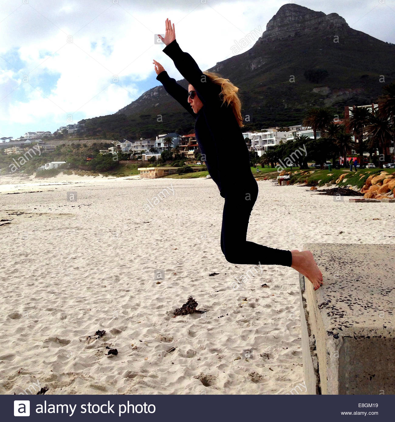 Woman jumping onto sand at beach - Stock Image