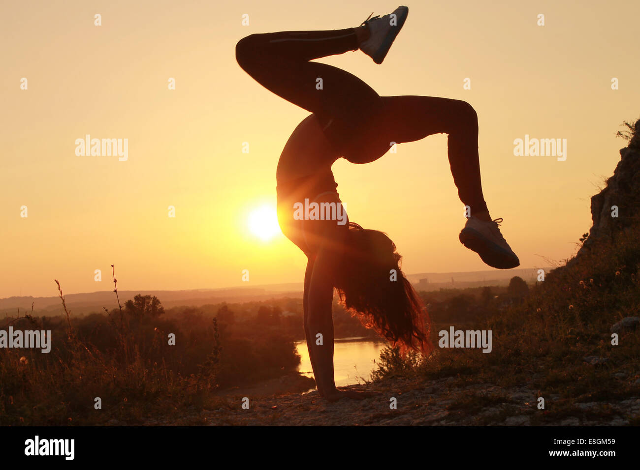 Young woman doing handstand at sunset Stock Photo