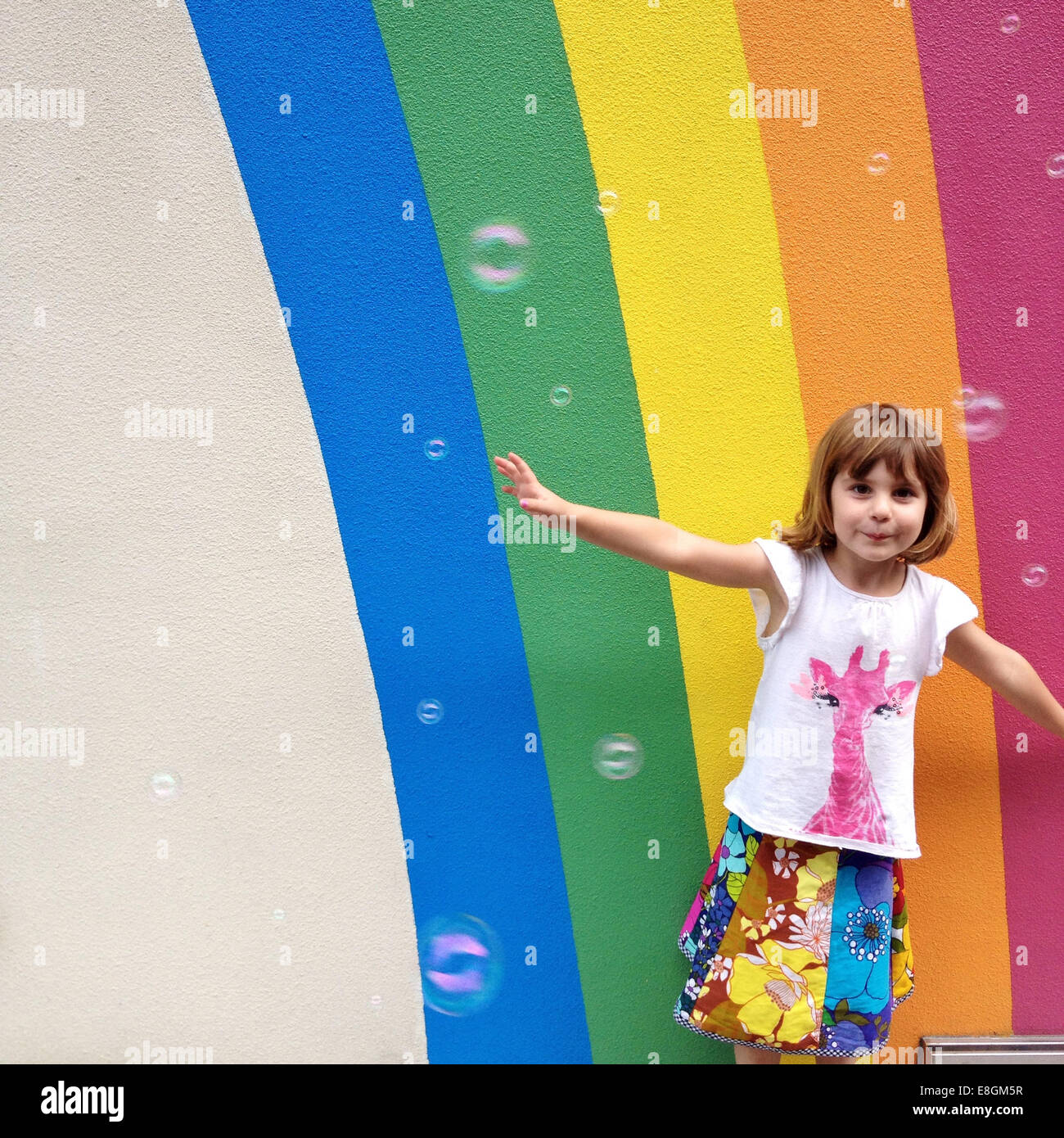 Girl (4-5) dancing with bubble in front of painted rainbow - Stock Image