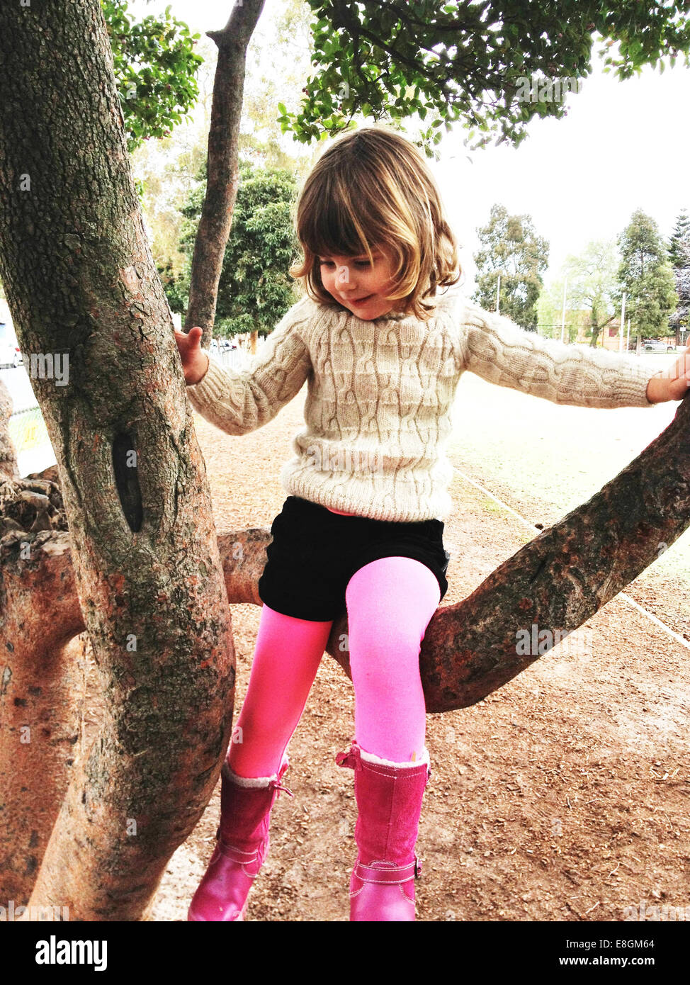 Girl (4-5) wearing pink boots climbing tree - Stock Image