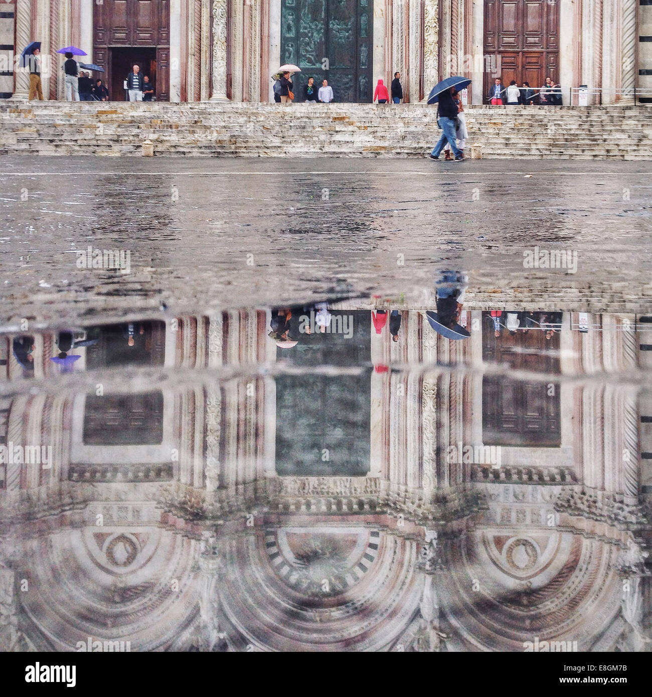 Italia, Tuscany, Siena, Cathedral reflected in puddle - Stock Image