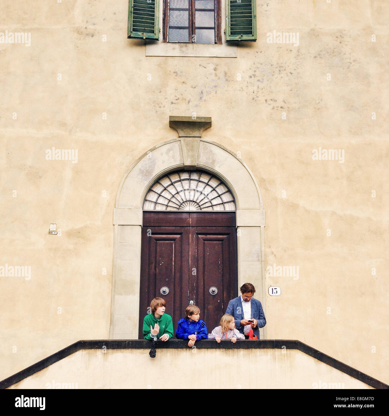 Italy, Florence, Father with three kids (10-11, 12-13) standing in front of building - Stock Image