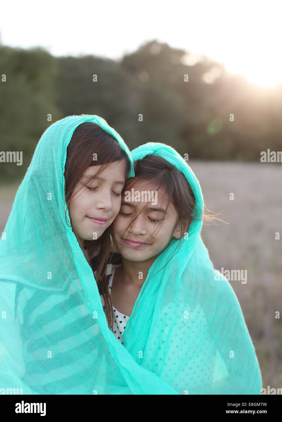 Two girls wrapped in a blanket - Stock Image