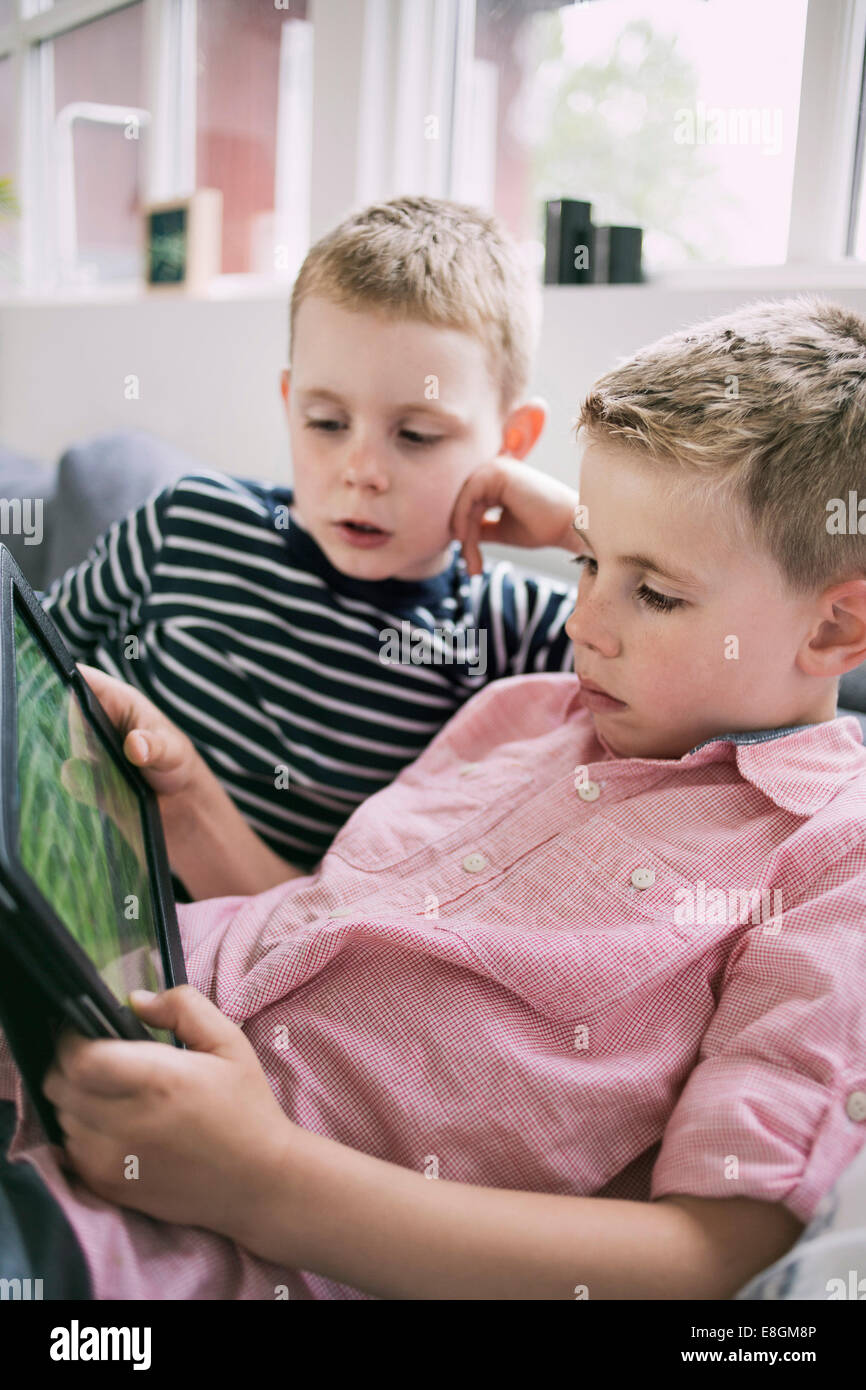 Brothers using digital tablet at home - Stock Image