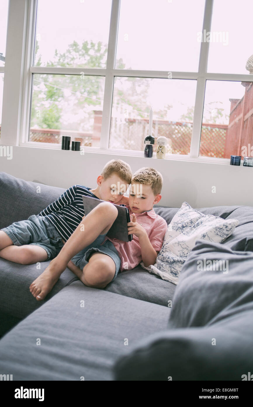Brothers using digital tablet on sofa at home - Stock Image