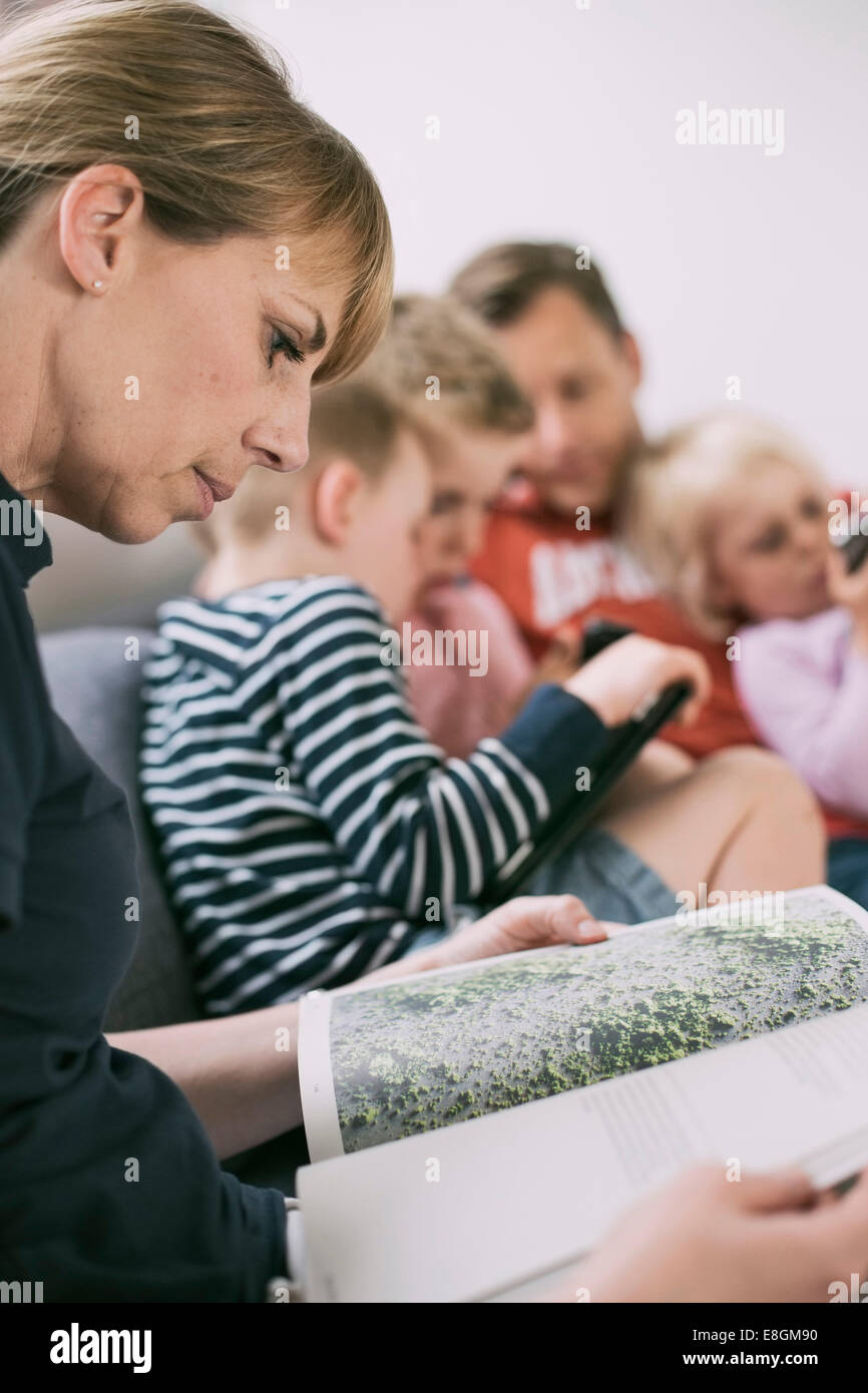 Side view of woman reading magazine with family using technologies in background - Stock Image