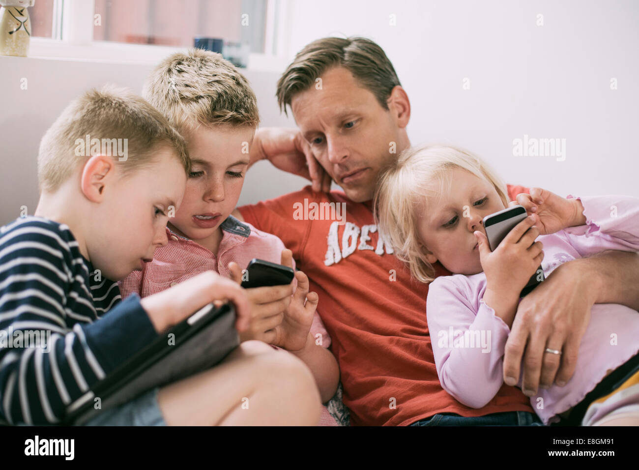 Father and children using technologies at home - Stock Image