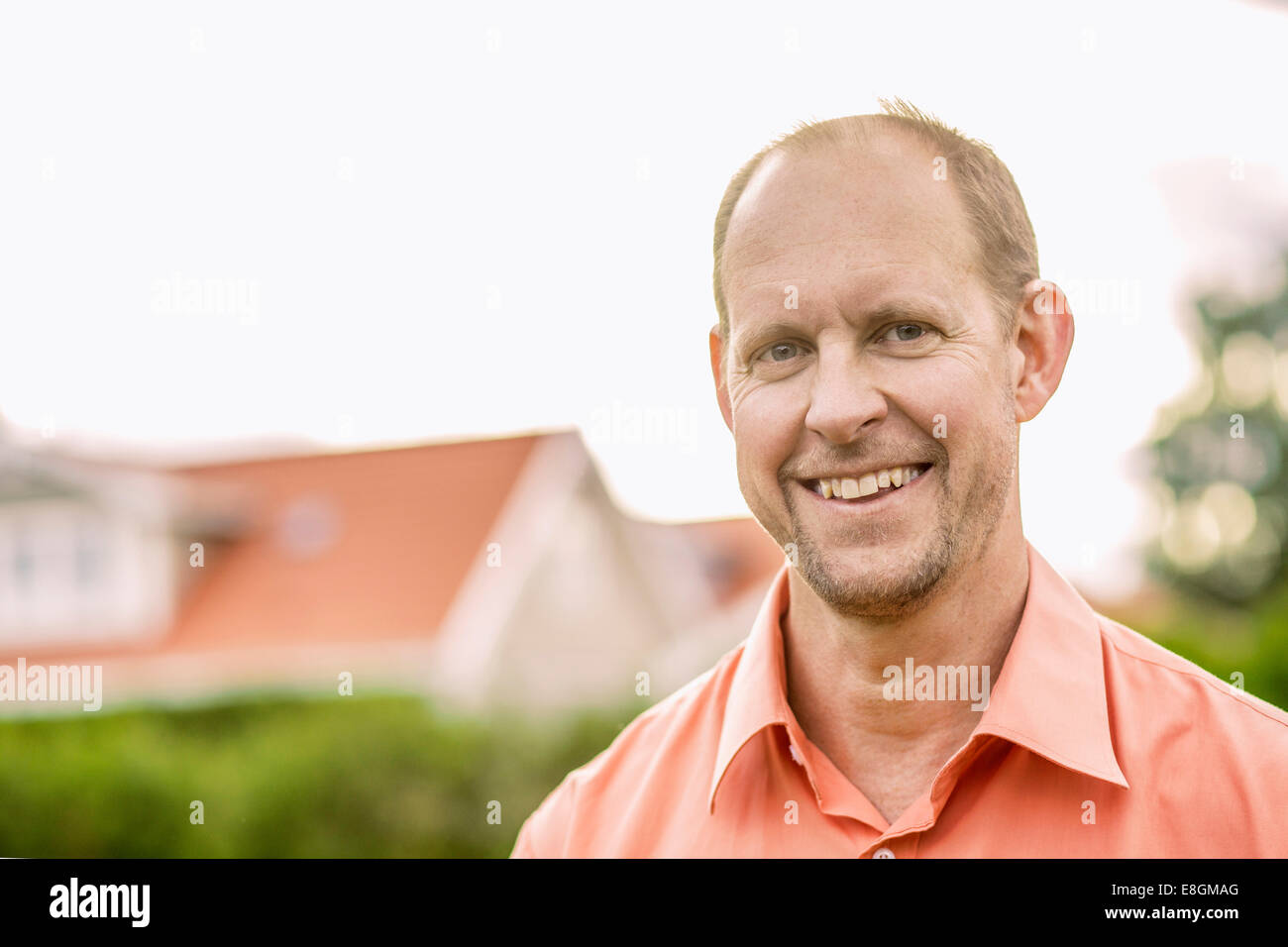 Portrait of mature man smiling in yard - Stock Image
