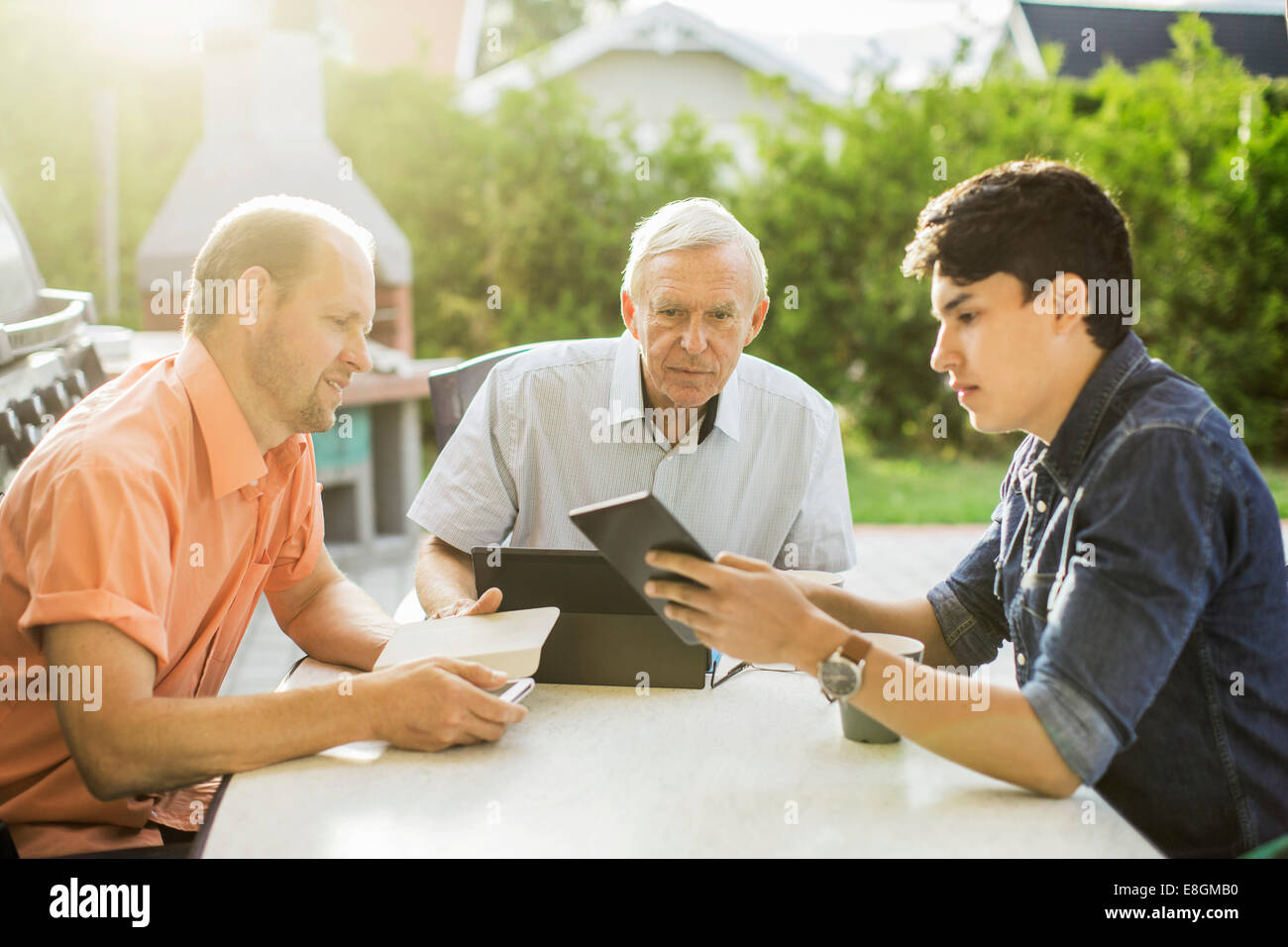 Three generation males using technologies at table in yard - Stock Image
