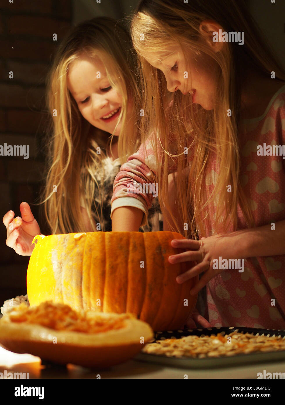 Sweden, Girls preparing (6-7), (8-9) the pumpkin for halloween - Stock Image