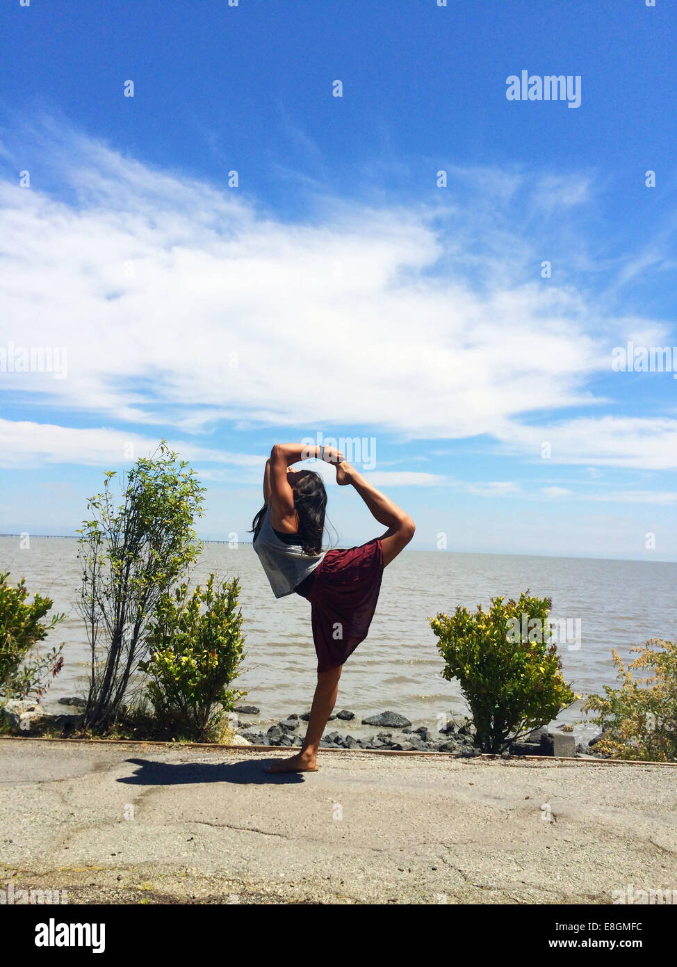 Girl doing standing bow pulling yoga pose on beach - Stock Image