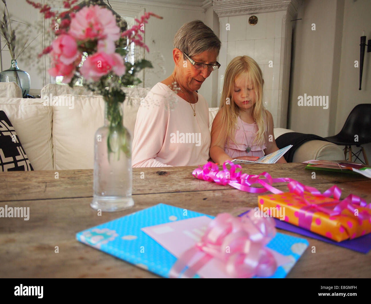 Grandmother reading book for her granddaughter (6-7) on her birthday - Stock Image