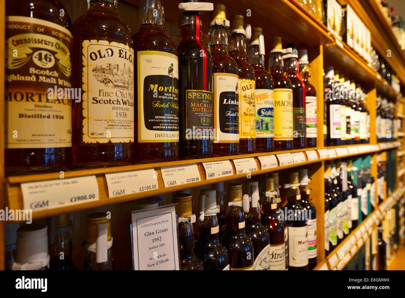 Whiskey bottles on the shelf, the headquarters of the whiskey bottler and distiller Gordon & MacPhail, Elgin, - Stock Image